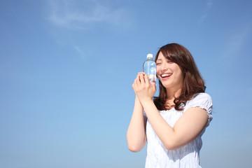 ペットボトルを持つ若い女性