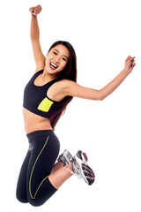 Girl in sportswear jumping with joy