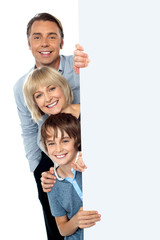 Family of three behind blank whiteboard