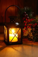Close-up of lantern with candle on wooden background.