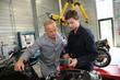 Teacher with students in mechanics working on bike