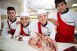 Leinwanddruck Bild - Happy team of young butchers in school kitchen