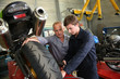 Постер, плакат: Teacher with students in mechanics working on bike