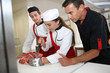Professional butcher teaching students with meat cutting