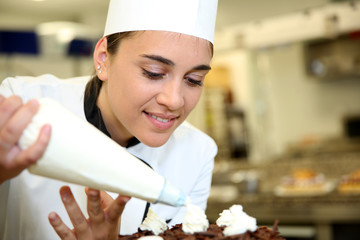 Pastry cook putting whipped cream on cake