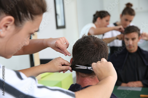 Student girl in hairdressing learning how to cut hair - 54038203