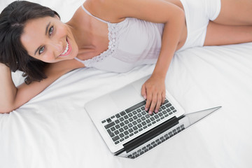 Portrait of a woman using her laptop lying in bed