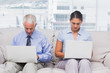 Business people sitting on sofa using their laptops
