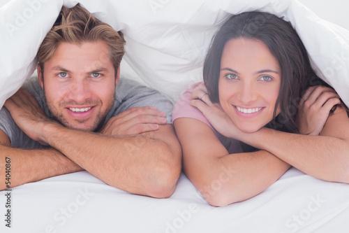 Couple smiling under the duvet