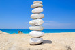 Pebbles stack balance over blue ionian sea in Greece