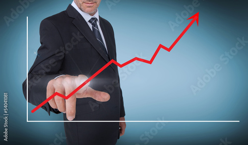 Businessman selecting a red arrow pointing up on a chart