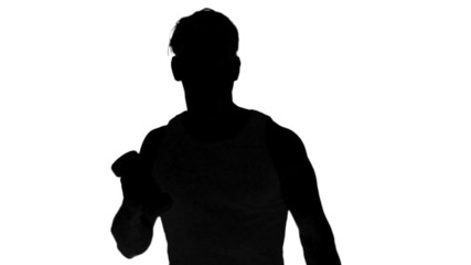 Silhouette of a man lifting dumbbells