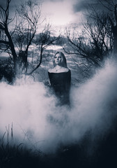Woman in black standing in the fog, monochromatic shot