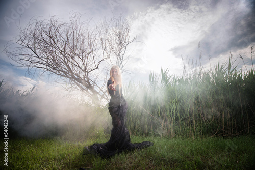 Weird female figure beckoning someone from the morning mist