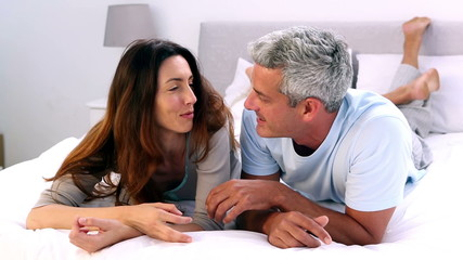 Couple talking and laughing on their bed