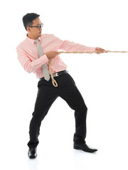 Asian businessman pulling a rope