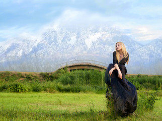 Woman in black dress, fairytale landscape on background