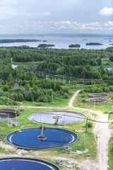 Water treatment plant and evergreen forest, aerial view