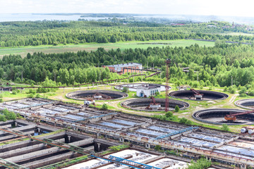 Water treatment plant in evergreen forest, aerial view, summer