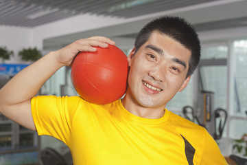 Man with ball on his shoulder in the gym