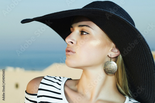 Beautiful woman in hat on the roof of Santorini island