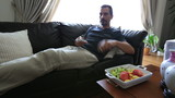 man eating fresh fruit and watching television