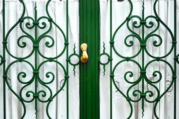Puerta con reja y llamador de bronce