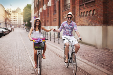 Happy young couple holding hands and riding on bike
