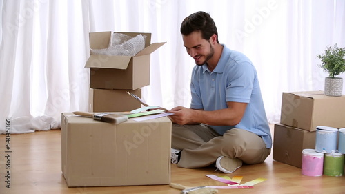 Man sitting on floor and choosing colour for his living room