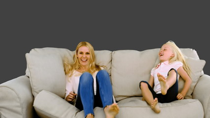 Mother and daughter jumping on the sofa on grey background