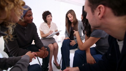 Woman therapist taking note in group therapy