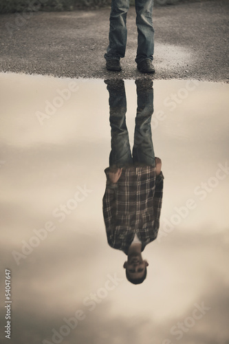 little boy standing in puddle