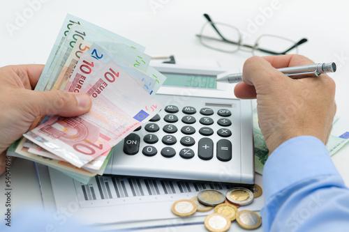 Hände mit Taschenrechner und Geld