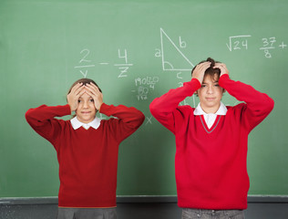 Confused Teenage Students Standing Against Board