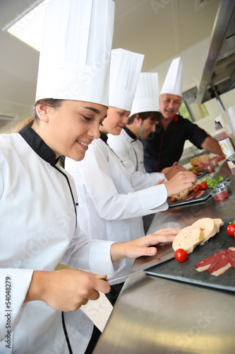 Team of young chefs preparing delicatessen dishes - 54048279