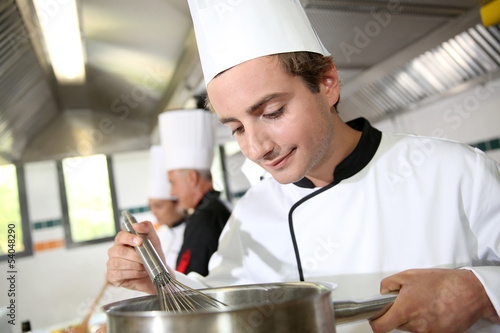 Young cook in restaurant kitchen preparing sauce