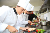 Fototapety Team of young chefs preparing delicatessen dishes