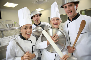 Team of young cooks being silly holding kitchenware