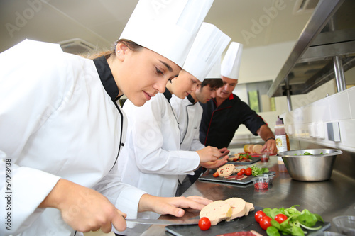canvas print picture Team of young chefs preparing delicatessen dishes