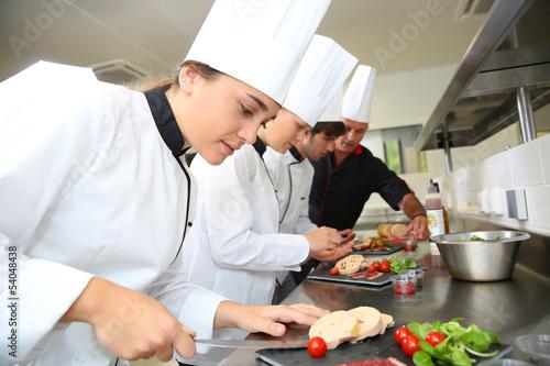 Leinwandbild Motiv Team of young chefs preparing delicatessen dishes