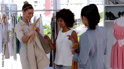 Pretty woman trying a jacket with friends
