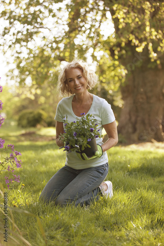 A mature woman holding a plant pot containing pansies