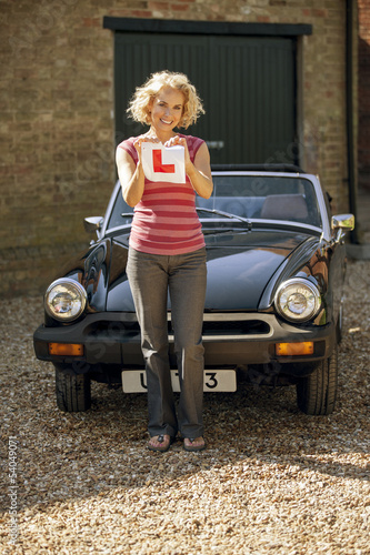 A mature woman tearing up a learner driver plate