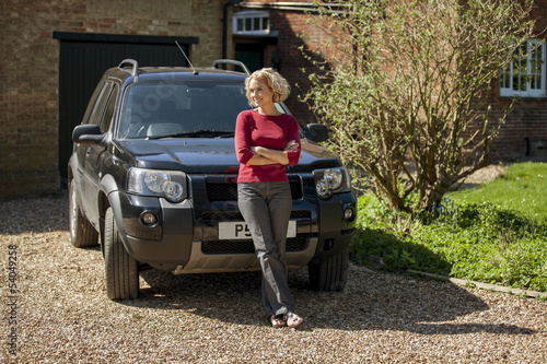A mature woman standing in the drive way of a house