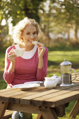 A mature woman having coffee and biscuits in a garden