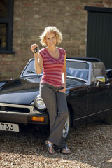 A mature woman holding the keys to classic sports car