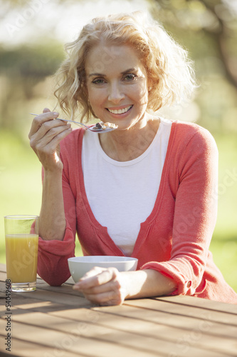 A mature woman eating breakfast outside