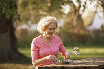 A mature woman sitting at a garden bench eating a meal