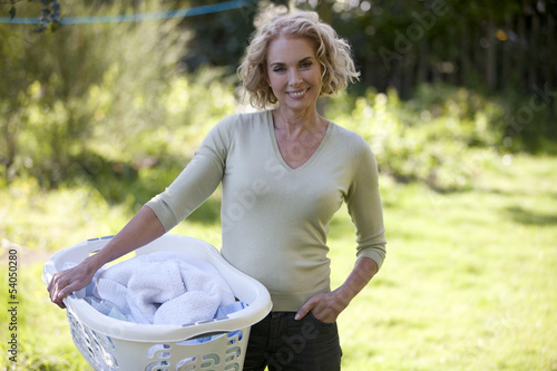 A mature woman holding a laundry basket outside