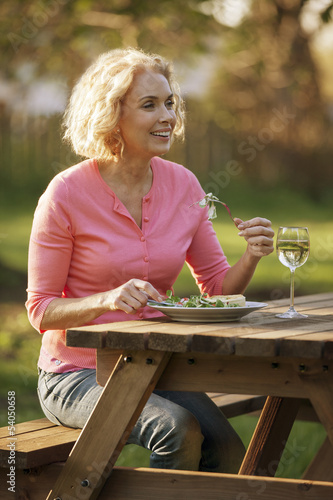 A mature woman eating a meal outside